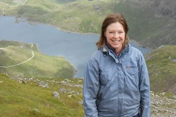 Katherine Robinson stands on top of a green mountain in Wales