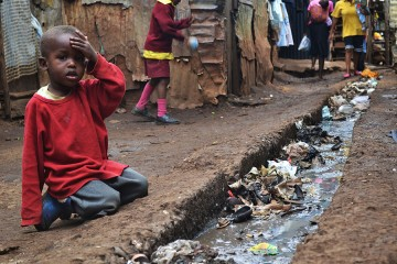 A young boy sits over an open sewer in the Kibera slum of Nairobi. The sewer is filled with trash and debris. The ground is packed dirt.