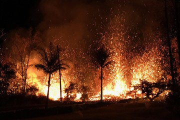 Sparks and lava burn palm trees