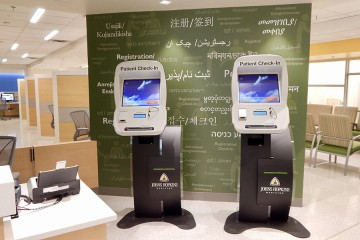 Two computer kiosks in from of dark green wall with words in various languages