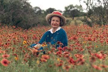 Lady Bird Johnson sits among a field of flowers