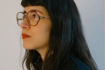 Side profile of Niege Borges, a woman with dark hair, red lipstick, and glasses