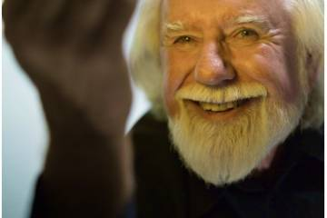 Photo of Alvy Ray Smith, an older white man with white hair, including facial hair, smiling and holding up his hand