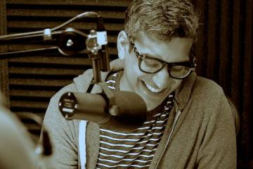 Sepia-toned photo of Mangesh Hattikudur, who is smiling and sitting behind a podcasting microphone
