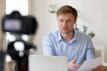 Man at desk facing laptop and camera