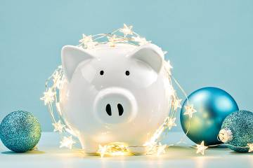 Piggybank decorated with start-shaped lights and Christmas tree balls