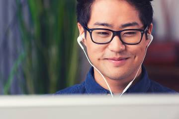 Man wearing earbuds looks at computer
