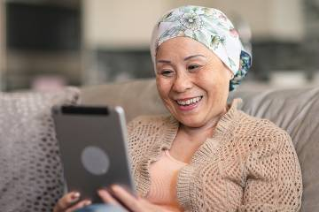 Woman with head wrapped in scarf smiling at the tablet she's watching