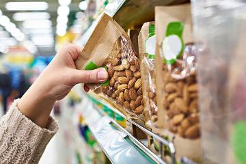 Hand taking a package of nuts off a store shelf