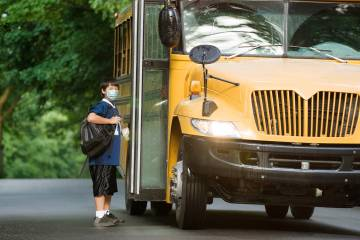 A masked boy boards a school bus