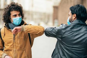 Two men in medical masks bump elbows in greeting
