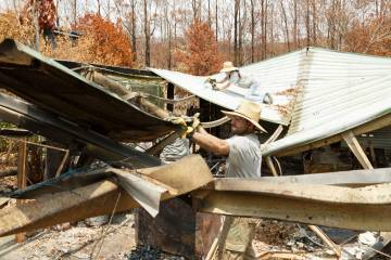 William McNulty sorts through the rubble of a destroyed house