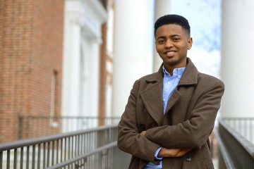 Melaku Arega in brown overcoat and light blue button-down shirt stands in front of white columns