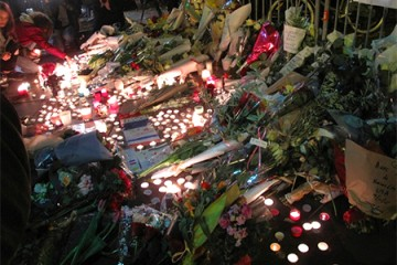 Memorial of candles, flowers, French flags