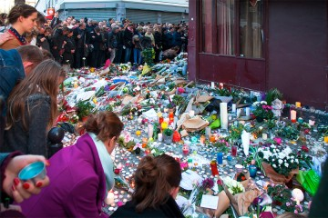Crowd around memorial of candles, flowers on Paris sidewalk