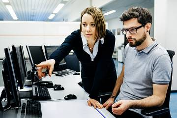 A woman helps a colleague with his work on a computer
