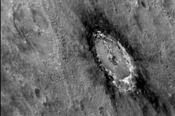 A black and white image of a crater in Mercury's surface, surrounded by dark marks at the rim of the crater.
