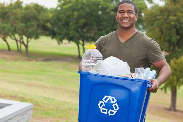 Man carrying recycling bin in a public park