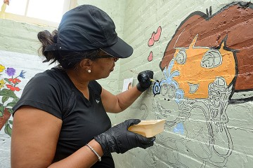 Cherita Hobbs paints a mural at the Family Recovery Program during the July launch of the Johns Hopkins Takes Time for Baltimore program.