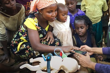 A mother in Uganda examines a cell-phone-like device next to an infant manikin