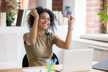 Happy employee looking at laptop and celebrating with arms raised