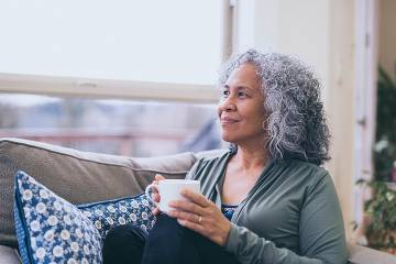 Thoughtful-looking woman holding a coffee mug