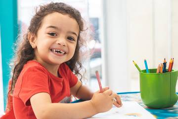 Young girl drawing with colored pencils
