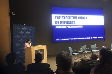 Nancy Kass stands at a podium in front of an audience