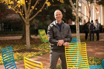 Photograph of Chris Nealon standing next to neon lawn chairs
