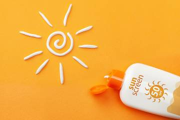 Bottle of sunscreen with a sun drawn in sunscreen