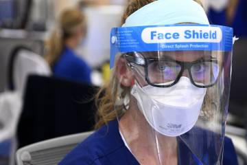 A nurse looks directly into the camera while wearing an N-95 mask and plastic splash shield