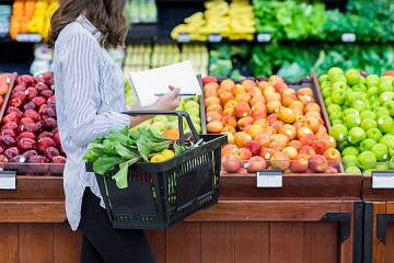 A woman in the grocery store fills her hand basket with produce