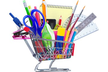A miniature shopping cart is filled with actual-size office supplies such as pens and scissors.