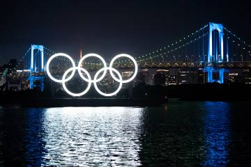 Olympic rings at night over water in Tokyo