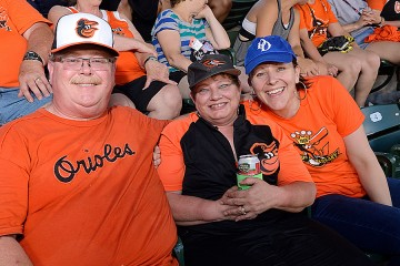 Three people in Orioles T-shirts photographed at a game