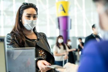 Woman wearing a protective medical mask hands documents to an airline ticket agent.