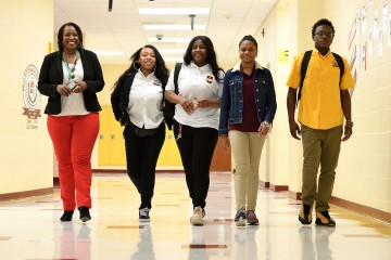 Photo shows Alexia Smith of the Johns Hopkins University Office of Community Affairs, with Dunbar High School students Caitlun Clark, Nayonna Earl, Simone Wade, and Alvin Winn