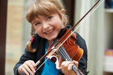 Smiling young girl with braids plays the violin