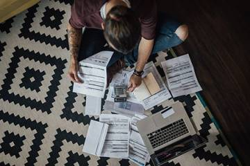 A person sits on the floor surrounded by bills, a calculator, and a laptop