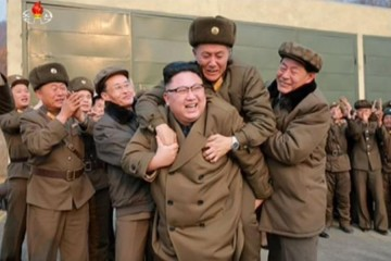 An older man in a military coat jumps on the back of a smiling Kim Jong-Un
