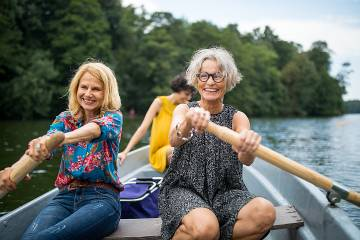 Two happy senior women rowing side-by-side