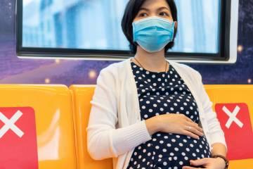 A pregnant woman rides public transit