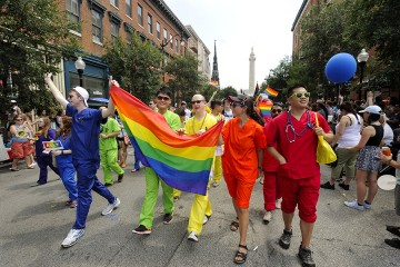 A group in blue, green, yellow, orange, and red scrubs hold the pride flag