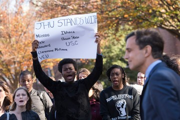 A student protester holds a sign that reads 'JHU stands with Mizzou, Yale, Howard, Claremont McKenna, VCA, Ithaca, Bowie State, USC'