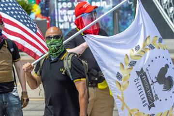 Pro-Trump protesters wear masks, military-style gear, and one carries a handgun