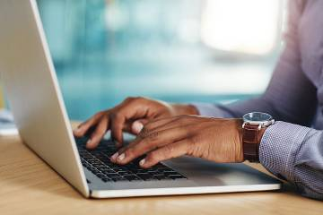 Closeup of man's hands using a laptop in an office