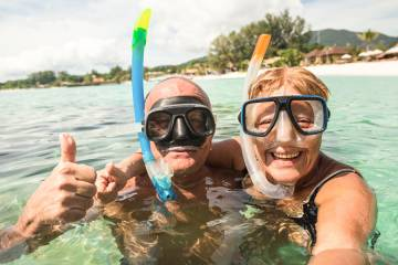 Smiling senior couple in sea wearing snorkels