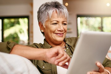 A lively-looking gray-haired woman is looking at a tablet screen
