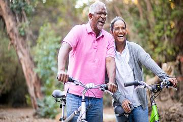 Mature man and woman riding bicycles