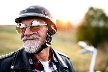Senior man with beard, sunglasses, and helmet on a motorcycle